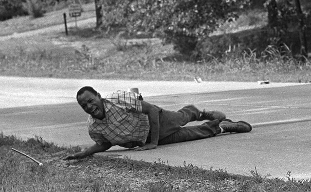 Civil rights activist James Meredith grimaces in pain as he pulls himself across Highway 51 after being shot in Hernando, Miss., June 6, 1966. Meredith was leading the March Against Fear to encourage African Americans to exercise their voting rights when he was shot. He completed the march from Memphis, Tenn., to Jackson, Miss., after treatment of his wounds. This photo won in 1967. (Photo by Jack Thornell/AP Photo)