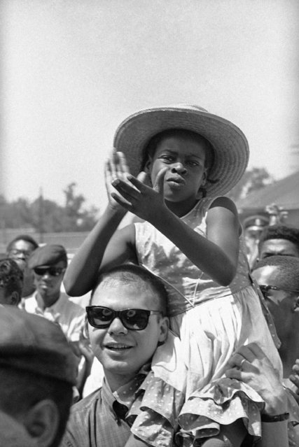 In this June 11, 1966 file photo, a girl claps as she sits on a fellow marcher's shoulder as the Meredith March moves along U.S. 51 near Batesville, Miss. James Meredith started the march from Memphis, Tenn., to Jackson, Miss., to encourage black people to overcome a fear of violence and to encourage them to register to vote. (Photo by AP Photo)