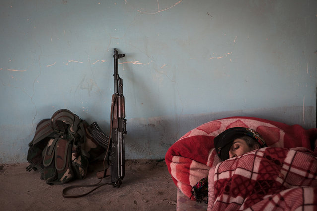YPJ soldier Shavin Bachouk, sleeps early in the morning at an abandoned Iraqi Army Post on the outskirts of Raabia, Syria, August 9, 2014. On the desolate Syrian-Kurdistan border live many YPG / YPJ soldiers, who are staked out at  makeshift posts to fend of IS attacks and protect the border. (Photo by Erin Trieb/NBC News)