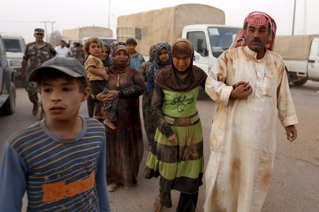 Syrian refugees covered with dust arrive at the Trabeel border, after they crossed into Jordanian territory with their families, near the northeastern Jordanian border with Syria, and Iraq, near the town of Ruwaished, east of Amman September 10, 2015. (Photo by Muhammad Hamed/Reuters)