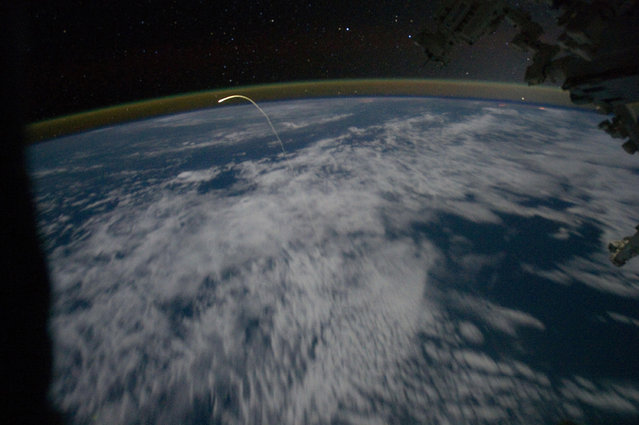 An unprecedented view of the space shuttle Atlantis, appearing like a bean sprout against clouds and city lights on its way home, as photographed from a window on the International Space Station on July 21, 2011. Airglow over Earth can be seen in the background. (Photo by Reuters/NASA)