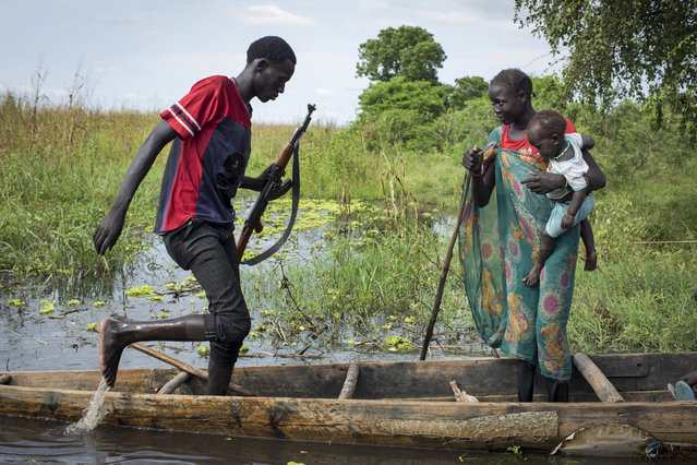 A woman and child from the Nuer ethnic group and a rebel soldier board a canoe to traverse flooded areas in order to reach a makeshift camp for the displaced situated in the United Nations Mission in South Sudan (UNMISS) base in the town of Bentiu, South Sudan Saturday, September 20, 2014. (Photo by Matthew Abbott/AP Photo)