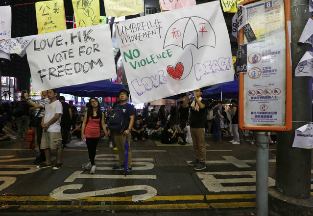"A poster with a drawing of an umbrella with the Chinese characters ""peace"" is displayed at a rally as protesters block the main road at Causeway Bay shopping district in Hong Kong September 30, 2014. (Photo by Bobby Yip/Reuters)"