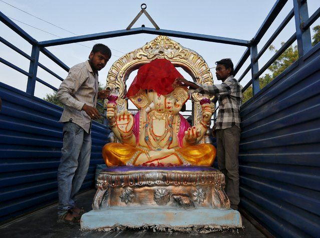 Workers load an idol of Hindu elephant god Ganesh, the deity of prosperity, onto a truck to transport it to a place of worship in Ahmedabad, India, September 16, 2015. (Photo by Amit Dave/Reuters)