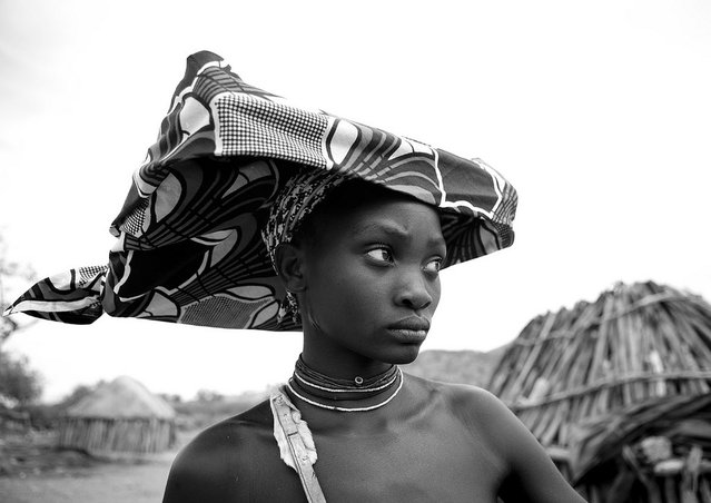 """Mucubal giant hat – Angola. Mucubal (also called Mucubai, Mucabale, Mugubale) people are a subgroup of the Herero ethnic group, which means they are bantu speaking, and are supposed to have come from Kenya and to be related with Massais"". (Eric Lafforgue)"