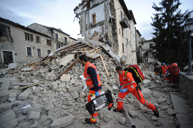 Rescuers search a crumbled building in Arcuata del Tronto, central Italy, where a 6.1 earthquake struck just after 3:30 a.m., Wednesday, August 24, 2016. The quake was felt across a broad section of central Italy, including the capital Rome where people in homes in the historic center felt a long swaying followed by aftershocks. (Photo by Sandro Perozzi/AP Photo)