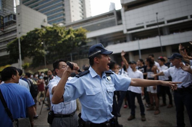 A police officer shouts at pro-democracy protesters at the main protest site in Admiralty in Hong Kong October 13, 2014. (Photo by Carlos Barria/Reuters)