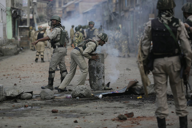 Indian government forces remove road blockades set by protesters during a clash after curfew was lifted in some parts of Srinagar in Indian-controlled Kashmir, Monday, August 29, 2016. Authorities on Monday lifted a curfew imposed in most parts of Indian-controlled Kashmir as part of a 52-day security lockdown, although most shops and businesses remained closed due to an ongoing strike called to protest Indian rule in the disputed Himalayan region. (Photo by Mukhtar Khan/AP Photo)