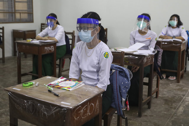 Students wearing face shields and masks attend a class by keeping social distancing at a high school in Yangon, Myanmar Tuesday, July 21, 2020. All the high schools in Myanmar reopened Tuesday following a closure due to the new coronavirus. (Photo by Thein Zaw/AP Photo)