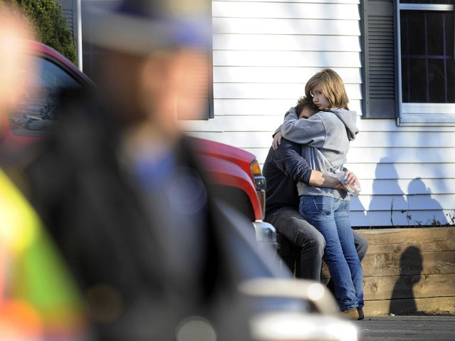 People embrace at a firehouse staging area near the scene of the shootings. (Photo by Jessica Hill/Associated Press)