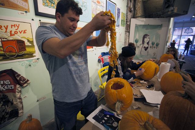 A workshop attendee pulls out innards from his pumpkin at Cotton Candy Machine in Brooklyn, N.Y. on October 18, 2014. (Photo by Siemond Chan/Yahoo Finance)