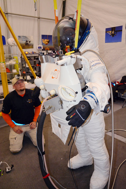 In this photo provided by Paragon Space Development Corporation, Google executive Alan Eustace, in the spacsuit, is shown with crewmember Mitch Sweeney in preparation his leap from the edge of space that broke the sound barrier and set several skydiving records over the southern New Mexico desert ourside Roswell Friday, October 24, 2014. (Photo by AP Photo/Paragon Space Development Corporation)
