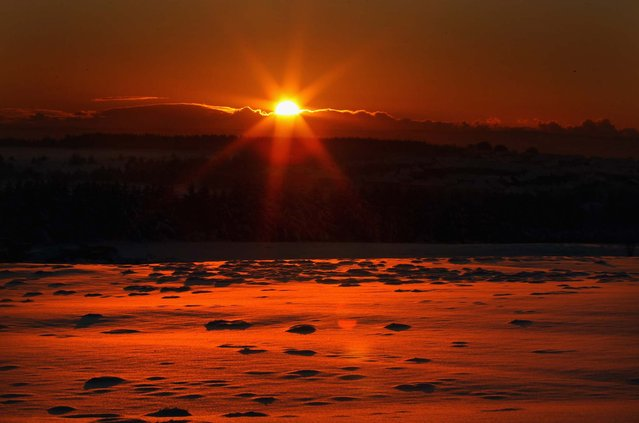 The sun sets over snow covered fields near the village of Salsburgh, Scotland on December 8, 2010. (Photo by Jeff J. Mitchell)