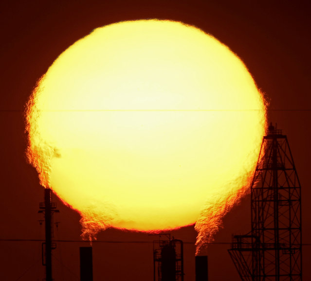 The sun sets behind the National Cooperative Refinery Association oil refinery Wednesday, August 19, 2015, in McPherson, Kan. (Photo by Charlie Riedel/AP Photo)