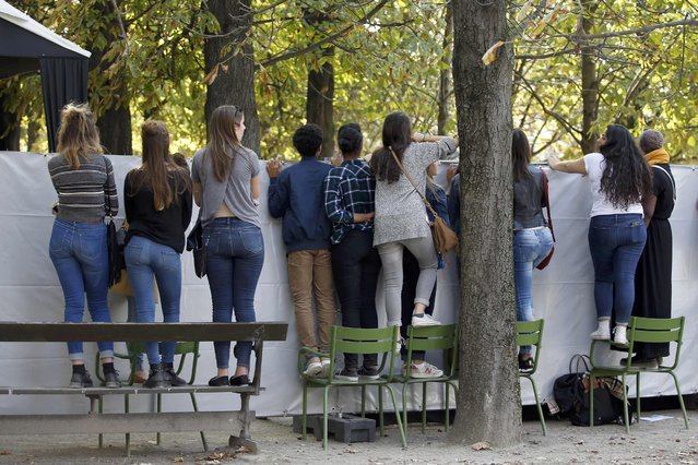 Fashion fans stand on charis as they watch models leaving after Elie Saab's Spring/Summer 2016 women's ready-to-wear collection during Fashion Week in Paris, France, October 3, 2015. (Photo by Charles Platiau/Reuters)