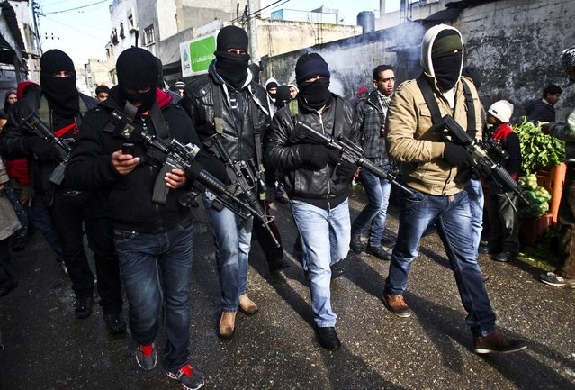 A group loyal to Palestinian leader Mahmoud Abbas' Fatah movement march in the Balata refugee camp in the West Bank, January 10, 2013. The men were protesting a recent campaign by Abbas to disarm renegade gunmen. (Photo by Nasser Ishtayeh/Assoicated Press)