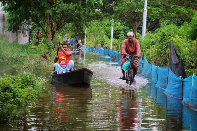 A man rides a bike on a submerged road alongside a boat at Demra area in Dhaka on July 24, 2020. As many as 20 districts including the latest additions Chandpur, Brahmanbaria, and Naogaon have so far been hit with the worsening flood situation across Bangladesh and many more areas might be inundated if the situation does not improve soon, said Flood Forecasting and Warning Centre (FFWC). (Photo by Sultan Mahmud Mukut/SOPA Images/LightRocket via Getty Images)