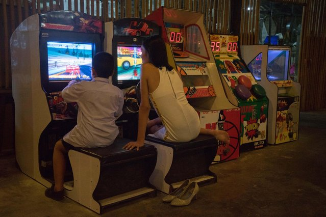 "Kritchaya ""Lolita"" Boonhor plays arcade games with the son of her father's friend, in Bangkok, Thailand, 28 November 2017. (Photo by Lola Levan/EPA/EFE)"
