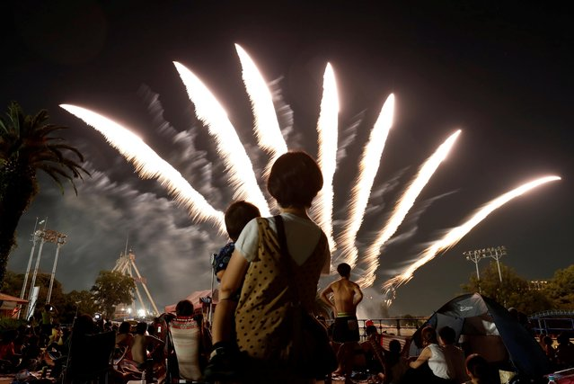 Visitors watch fireworks, amid the coronavirus disease (COVID-19) outbreak, at Toshimaen amusement park which will close 94 years after it first opened with part of the site be turned into a new Harry Potter theme park in 2023, in Tokyo, Japan on August 21, 2020. (Photo by Issei Kato/Reuters)