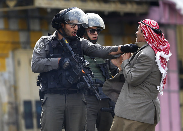 A Palestinian is pushed an Israeli policemen amid clashes in Hebron, West Bank, Saturday, October 10, 2015. A Palestinian teenager stabbed two Israelis in Jerusalem Saturday before being shot dead by police forces, the latest in a series of stabbing attacks against civilians and soldiers that have spread across Israel and the West Bank in the past week. (Photoby Nasser Shiyoukhi/AP Photo)