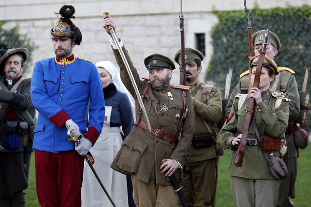 """History enthusiasts of Russian association """"Na Zapad"""" and British volunteers dressed in Russian vintage uniforms attend an Armistice Day ceremony to commemorate the end of World War One at the American Monument upon hill 104 near Chateau Thierry, eastern France, November 11, 2014. (Photo by Charles Platiau/Reuters)"""
