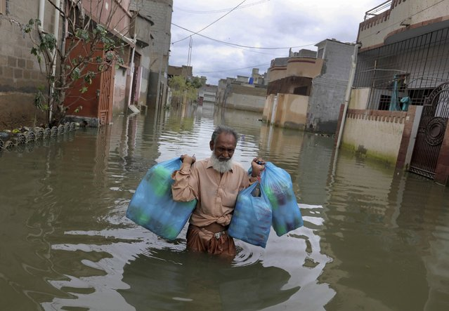 A man carries goods as he wades through flooded street after heavy monsoon rains, in Karachi, Pakistan, Wednesday, August 26, 2020. Pakistan's military said it will deploy rescue helicopters to Karachi to transport some 200 families to safety after canal waters flooded the city amid monsoon rains. (Photo by Fareed Khan/AP Photo)