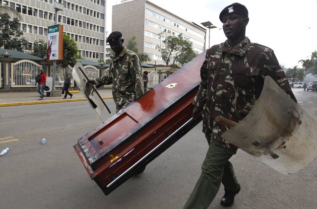 Riot police officers remove a coffin left behind by protestors during the #OccupyHarambeeAve demonstration in Kenya's capital Nairobi November 25, 2014. (Photo by Thomas Mukoya/Reuters)