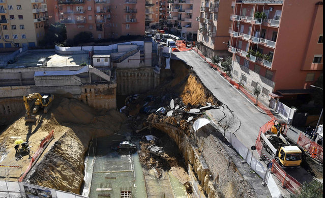 The picture taken on February 15, 2018 in the street of Balduina' s district in Rome shows a general view of a huge sinkhole that opened up the day before in Rome, swallowing six cars. No casualties were reported About 22 families were evacuated by firefighters following the collapse. The cause of the sinkhole is still under investigation. (Photo by Tiziana Fabi/AFP Photo)