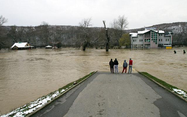 Villagers look at flooded houses pictured in the village Guri i Zi, in the western part of Kosovo on Friday, March 15, 2013. A 8-year-old girl drowned after days off heavy rain fall swelled a river in the northern town of Skenderaj, and  flooded many areas in Kosovo. (Photo by Visar Kryeziu/AP Photo)