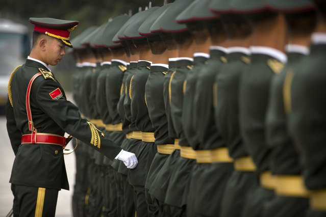 An officer adjusts the uniform of a Chinese honor guard member before a welcome ceremony for Belarusian President Alexander Lukashenko at the Great Hall of the People in Beijing, Thursday, September 29, 2016. (Photo by Mark Schiefelbein/AP Photo)
