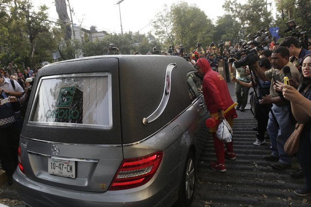 "A man dressed as ""El Chapulin Colorado"", a character by screenwriter Roberto Gomez Bolanos, peers into a funeral van carrying the body of Bolanos as they arrive at Mexican media company Televisa in Mexico City November 29, 2014. (Photo by Carlos Jasso/Reuters)"