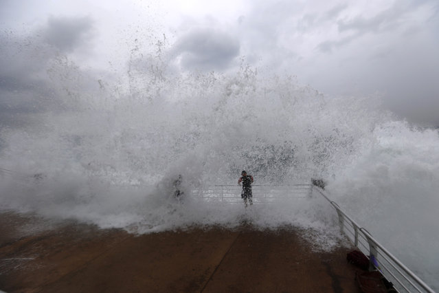Lebanese men workout as waves crash over them on the seafront at the Corniche, or waterfront promenade, in Beirut, Lebanon, Sunday, October 25, 2015. (Photo by Hassan Ammar/AP Photo)