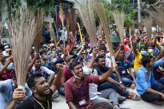 Garment workers shout slogans while holding brooms during a protest demanding their due wages in Dhaka, Bangladesh, September 7, 2020. (Photo by Mohammad Ponir Hossain/Reuters)