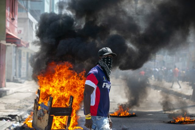 A protester walks past burning barricades during a protest demanding the resignation of President Jovenel Moise in Port-au-Prince, Haiti, Saturday, October 17, 2020. The country is currently experiencing a political impasse without a parliament and is now run entirely by decree under Moise. (Photo by Dieu Nalio Chery/AP Photo)
