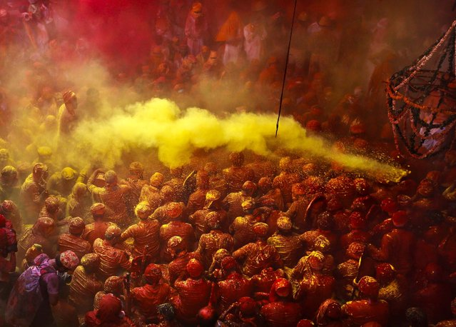 Hindu men from the village of Nandgaon are covered in colored powder as they sit on the floor during prayers at the Ladali before the procession for the Lathmar Holi festival. (Photo by Kevin Frayer/Associated Press)