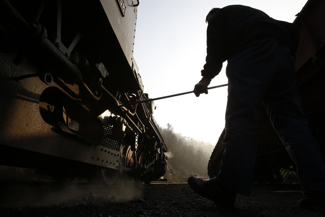 Bosnian worker Sefik Salihovic prepares a steam engine for driving inside a coal mine Oskova in the Bosnian town of Banovici, 140 kms (86.9 miles) north of Sarajevo, on Monday November 24, 2014. (Photo by Amel Emric/AP Photo)
