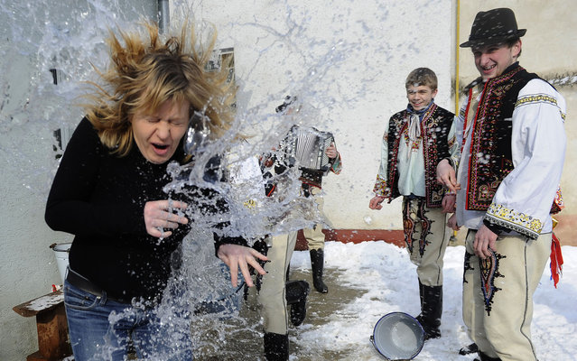 Young Slovak men dressed in traditional costumes pour a bucket with cold water over a woman as part of Easter celebrations in the village of Trencianska Tepla, 145 km north of Bratislava on April 1, 2013. Slovakia's men traditionally splash women with water and hit them with a willow to evoke youth, strength and beauty for the upcoming spring season. (Photo by Samuel Kubani/AFP Photo)