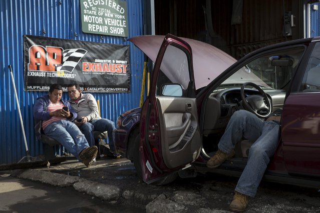 Men look at a cellular device as a worker tends to an automobile in the Willets Point area of Queens in New York October 29, 2015. (Photo by Andrew Kelly/Reuters)