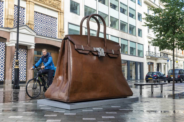 A man cycles past the Kalliopi Lemos Bag of Aspirations Mild steel and stainless steel, a giant handbag sculpture on display on the corner of New Bond Street and Brook Street in London on October 8, 2020. (Photo by Dave Rushen/SOPA Images/LightRocket via Getty Images)