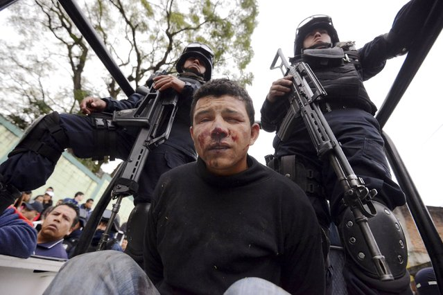 A man, who was beaten up by residents, sits guarded by two police officers in the back of a police truck in Xalapa, Mexico, December 10, 2014. The man, accused of being part of a group of people who had kidnapped an 11-year-old school girl, was grabbed from a car, as the group tried to flee the area, by infuriated neighbors who beat him up until the police arrived, according to local media. (Photo by Oscar Martinez/Reuters)