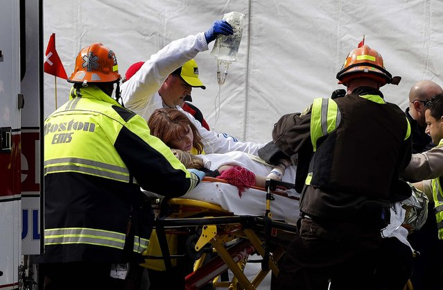 An injured woman is loaded into an ambulance in the aftermath of the two blasts. (Photo by Elise Amendola/Associated Press)