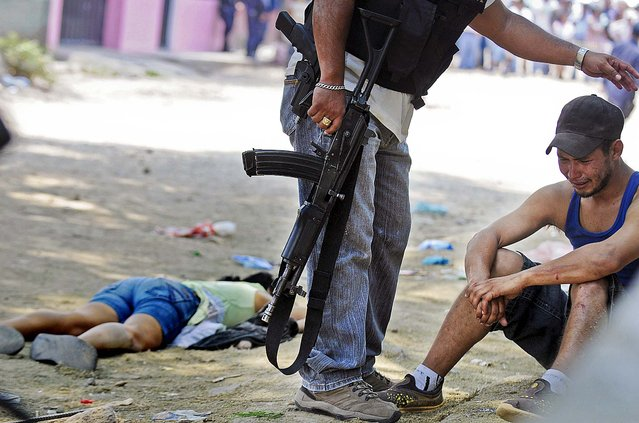 A policeman comforts a man next to the body of Maria Duron, a pregnant fruit vendor caught in the crossfire after gunmen opened fire on a vehicle, killing a sixteen year-old student, her police bodyguard and three other people who were on the street in the city of Tegucigalpa, Honduras, on April 15, 2013. (Photo by Fernando Antonio/Associated Press)