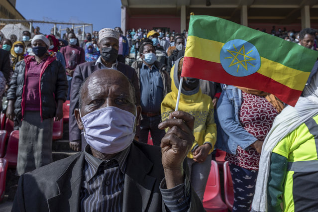 A man holds a national flag as he waits in the stands to give blood at a blood drive in support of the country's military, at a stadium in the capital Addis Ababa, Ethiopia Thursday, November 12, 2020. (Photo by Mulugeta Ayene/AP Photo)