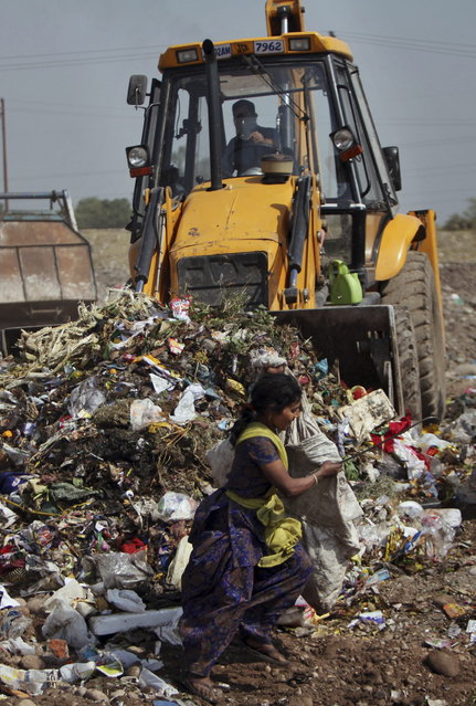 A young Indian rag carries bags filled with reusable materials as a backhoe pushes garbage at a dump yard on the outskirts of Jammu, India, Monday, April 22, 2013. April 22 is observed as Earth Day every year as a tool to raise ecological awareness. (Photo by Channi Anand/AP Photo)