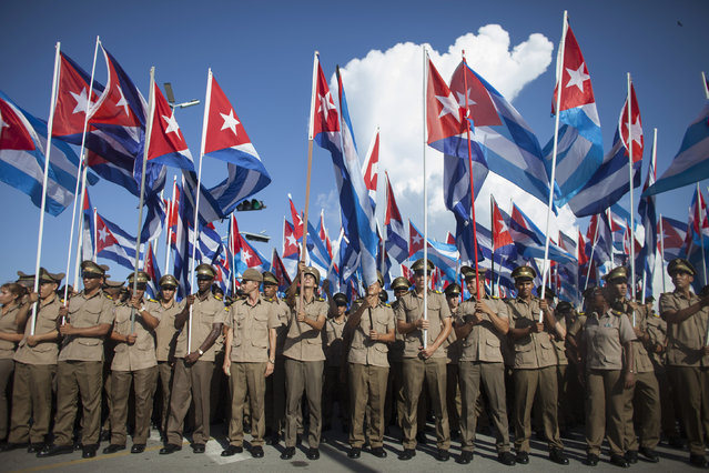 "Members of the Cuban Revolutionary Army hold Cuban national flags during a march ""For the Five and Against the Terrorism"" in Havana September 30, 2014. (Photo by Alexandre Meneghini/Reuters)"