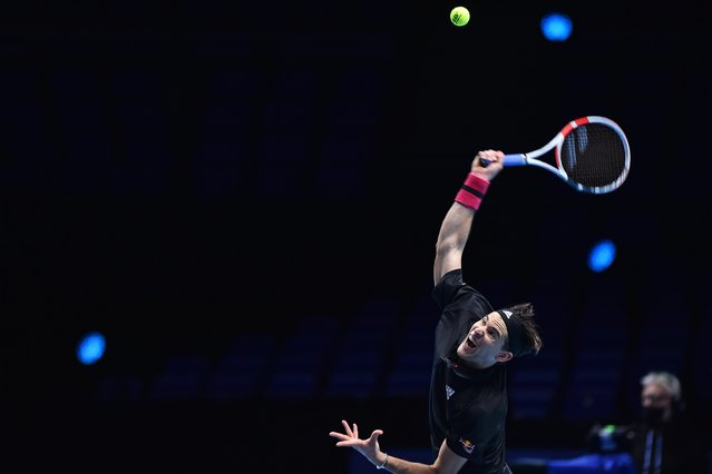 Austria's Dominic Thiem serves against Greece's Stefanos Tsitsipas in their men's singles round-robin match on day one of the ATP World Tour Finals tennis tournament at the O2 Arena in London on November 15, 2020. (Photo by Glyn Kirk/AFP Photo)
