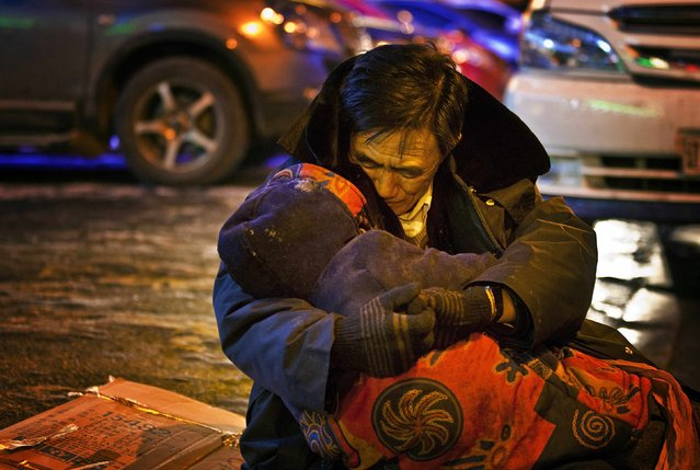 A man, whose surname is He, cuddles the body of his dead wife during a sub-zero evening in Shenyang, Liaoning province December 17, 2014. The man sat by the roadside while holding his wife's body for almost two hours till his son came and persuaded him to bring the body home, according to local media. The wife had just bought medicine from a pharmacy when she collapsed in a street and died of heart failure. (Photo by Reuters/Stringer)