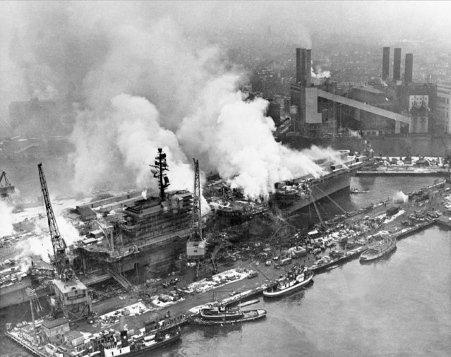 Smoke rises from the fire aboard the navy aircraft carrier USS Constellation at the Brooklyn Navy Yard on the East River in New York, December 19, 1960. In the background is part of the Brooklyn waterfront.  The fire began after a forklift collided with fuel tank as construction of the carrier neared completion. Fifty people were killed and hundreds injured. (Photo by AP Photo)
