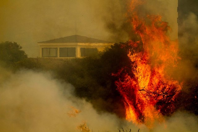 Flame and smoke rise from The Naval Base at Point Mugu. The 15 1/2-square-mile blaze was only 10 percent contained on Friday, and the work of more than 900 firefighters, aided by air tankers, was just beginning. (Photo by Ringo H.W. Chiu/Associated Press)
