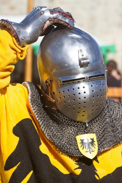 "A German contestant adjusts his helmet during the ""Battle of Nations"" in Aigues-Mortes, southern France, Friday, May 10, 2013 where Middle Ages fans attend the historical medieval battle  competition. The championship will be attended by 22 national teams, which is twice the number it was last year. The battle lasts until May 12. (Photo by Philippe Farjon/AP Photo)"